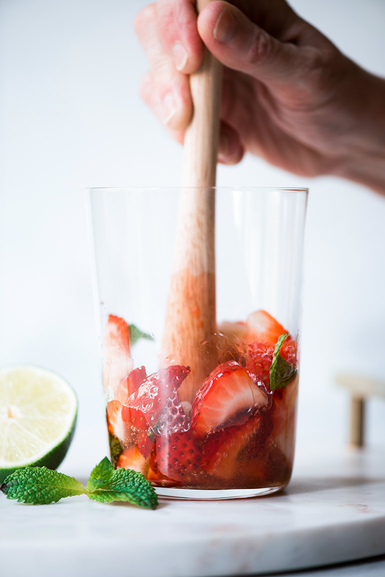 muddling mint and strawberries for mojitos