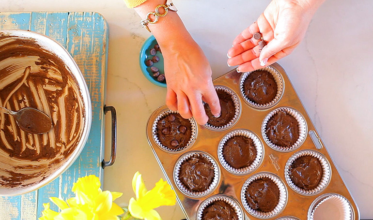 adding chocolate chips to chocolate avocado muffins