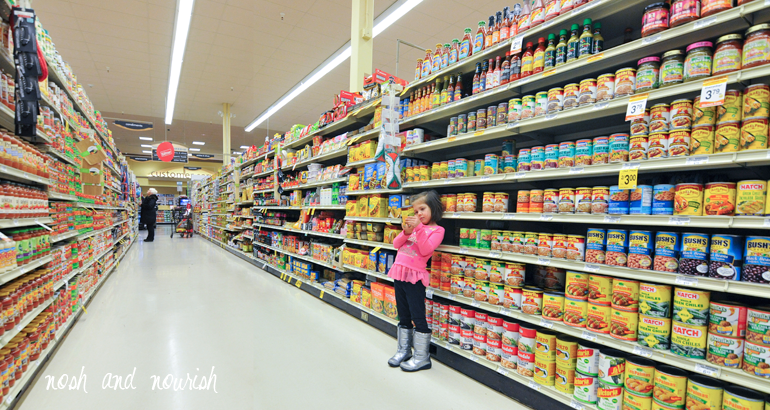 child reading nutrition labels at grocery store