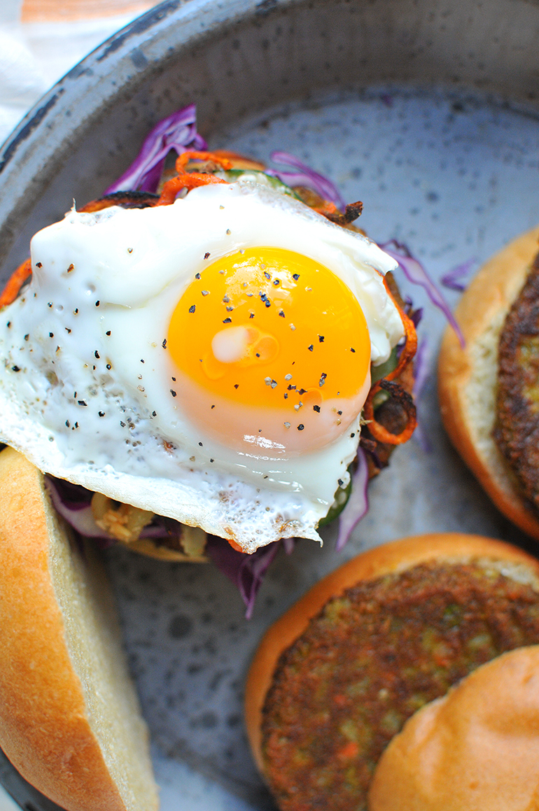korean bbq bibimbap burgers with fried eggs on top