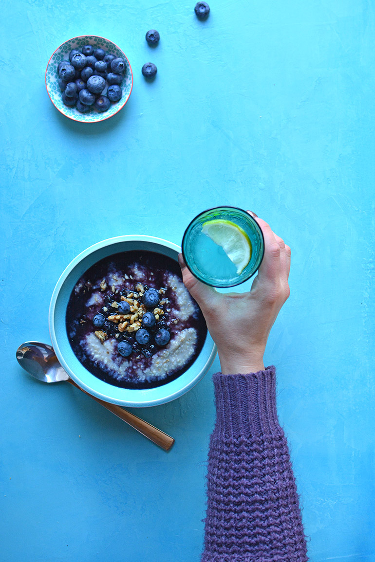 blueberry oatmeal bowl with a glass of lime water