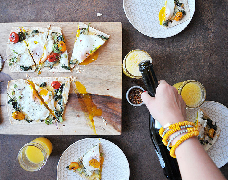 pouring mimosas with breakfast pizza