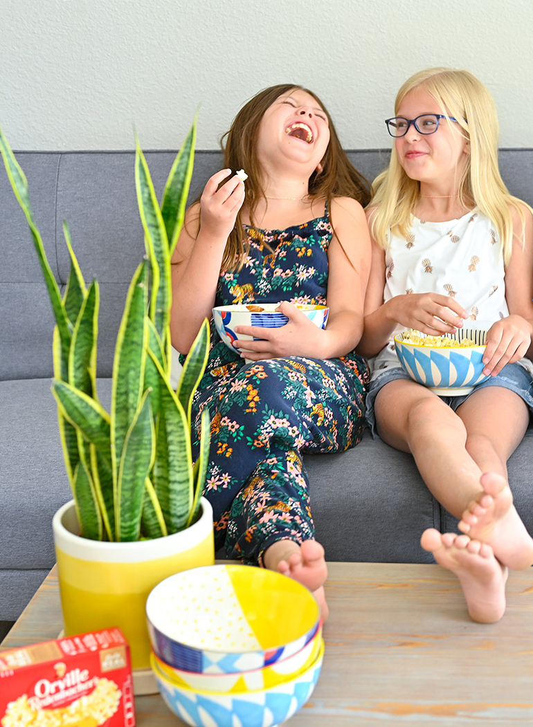 girls laughing on couch with popcorn bowls